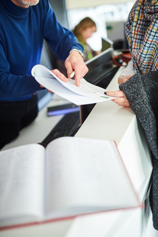 Een man toont een brochure aan een klant