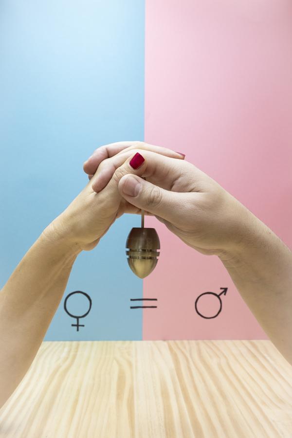 De handen van een man en een vrouw die een gewicht vasthouden naast het symbool van gendergelijkheid