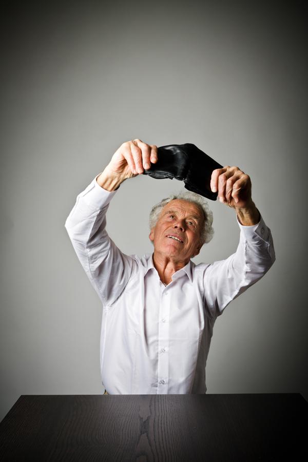 Oudere man die een lege portefeuille toont