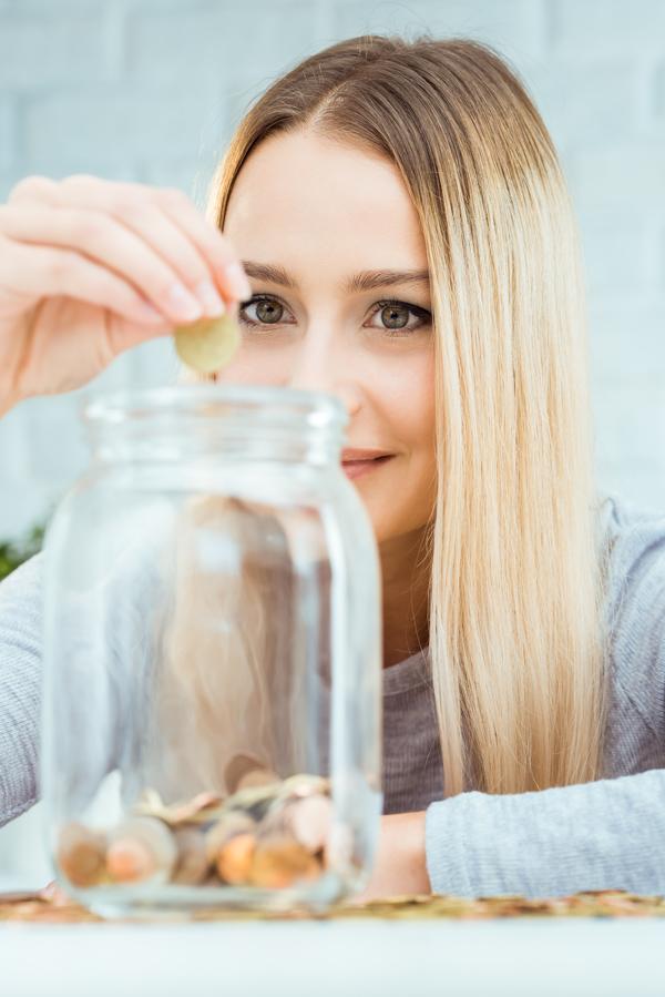Jonge vrouw die muntstukken in een glazen bokaal stopt