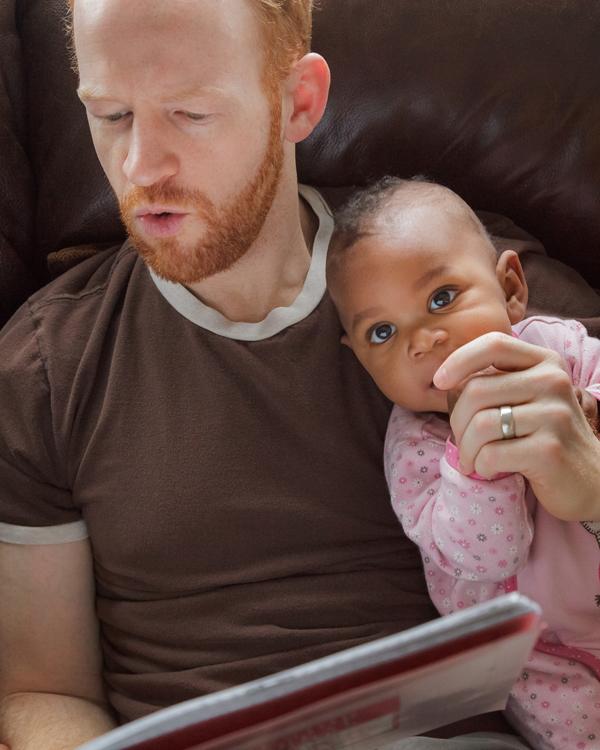Een vader leest een verhaaltje voor aan zijn baby