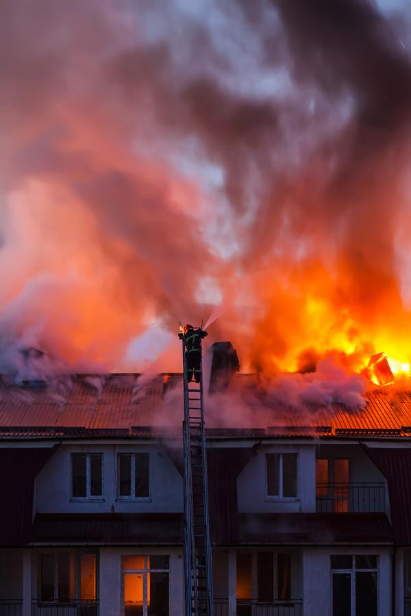 Brandend dak van een huis, met op een ladder een brandweerman die de brand blust