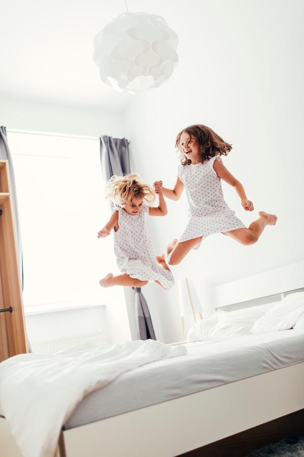 Twee kleine meisjes die zich amuseren door op een groot bed te springen