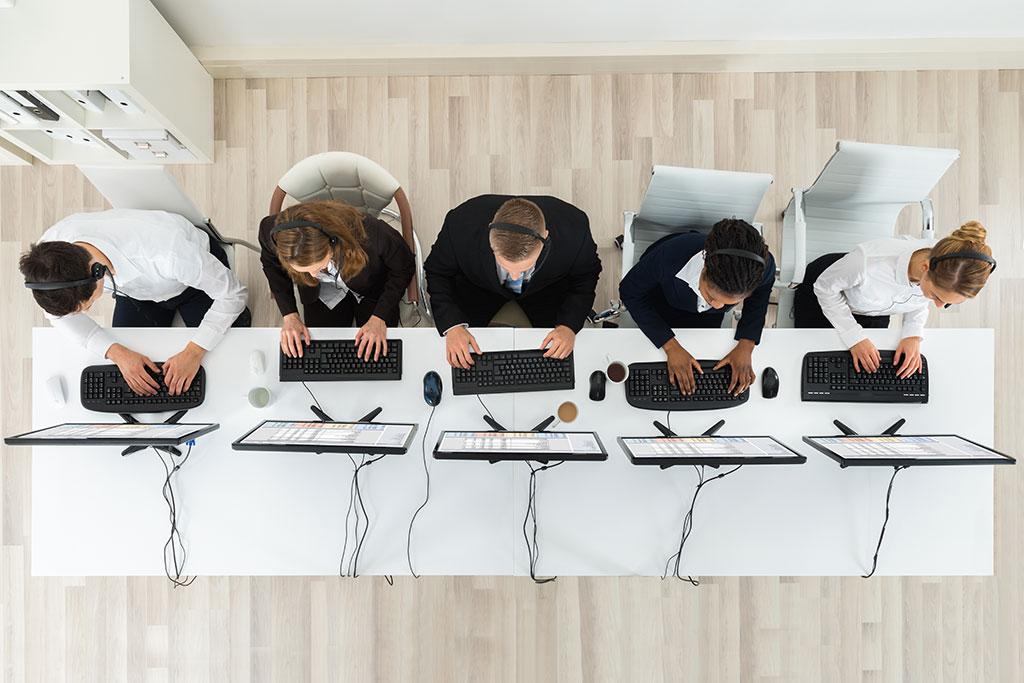 5 personen die op pc aan het werken zijn