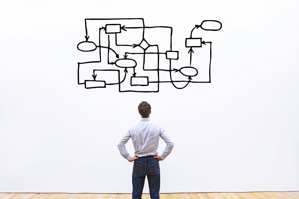 Man voor een muur, die een bijzonder ingewikkeld schema bekijkt