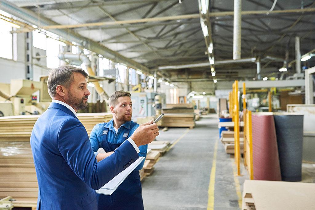 Een man die een bedrijf controleert en daarbij wordt vergezeld door een arbeider van het bedrijf