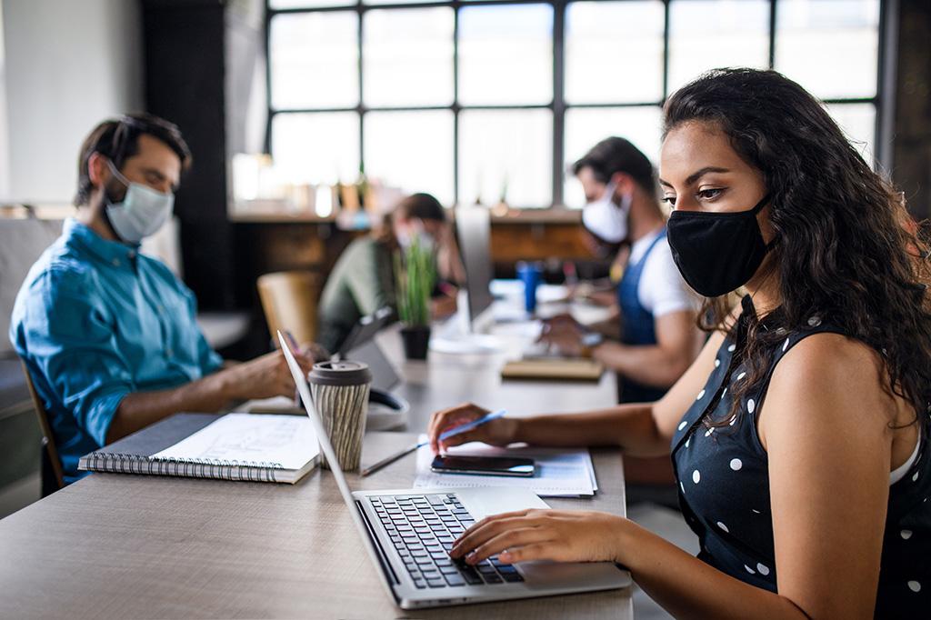 werknemers die werken met sociale distantie en maskeren